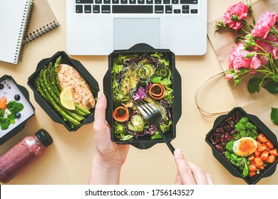 Female hands hold food delivery box having lunch at work from home office. Business woman worker eats salad take away nutrition daily healthy meal weight loss diet menu at workplace flat lay top view.