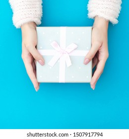 Female hands hold a gift box.