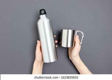 Female hands hold metal bottle and mug. Minimalistic concept on dark gray background.