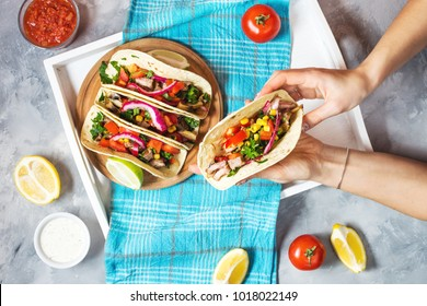 Female hands hold mexican pork tacos with vegetables on wooden blue background. Top view
