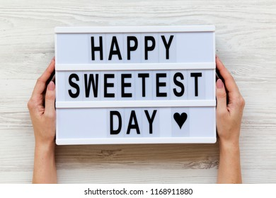 Female hands hold modern board with text 'Happy Sweetest Day' word over white wooden background, top view. From above, flat lay, overhead.