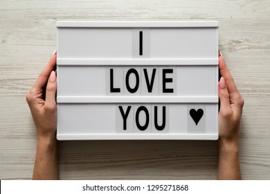 Female hands hold modern board with text 'I Love You' on a white wooden surface, top view. Flat lay, overhead. Valentine's Day 14 February.