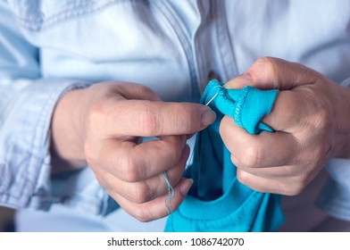Female hands hold a needle with a thread and some clothes to mend it