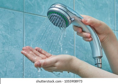 Female hands hold a new shower head and try the water temperature in the bathroom with blue walls.