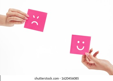 female hands hold notes with painted emoticons, the concept of a good and bad day, mood, work