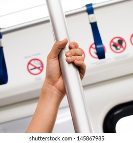 female hands hold on to pole in train in train