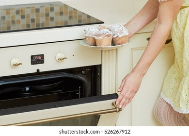 Female hands hold plate with homemade baked cupcakes and closes door of oven in kitchen.