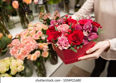 Female hands hold red box with flowers