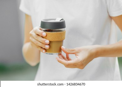 Female hands hold reusable coffee mug. Take your coffee to-go with reusable travel mug. Zero waste. Sustainable lifestyle concept.