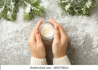 Female hands hold scented candle on gray background with snow and pine branches