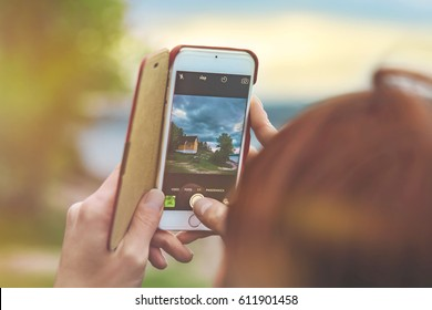 Female hands hold the smart phone while shooting a landscape in Norway at sunset light