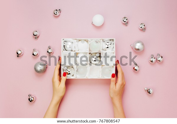 Female hands hold Stylish set of shiny silver christmas balls. Holiday concepts.  Flat lay, top view