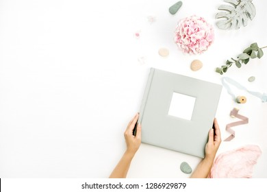 Female hands hold wedding or family photo album. Composition with hydrangea flower bouquet, eucalyptus branch, pastel pink blanket, monstera leaf plate on white background. Flat lay, top view.