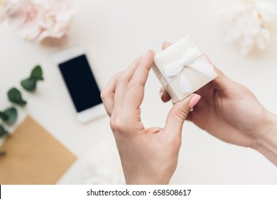 Female hands hold white gift box on background of flowers and phone. top view