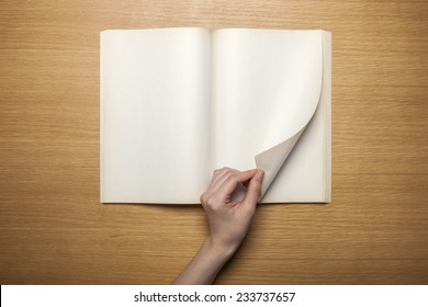 A female hands hold(grip) a vintage(old) book(note, diary) spread and through the pages of a book on the wooden desk, top view at the studio.