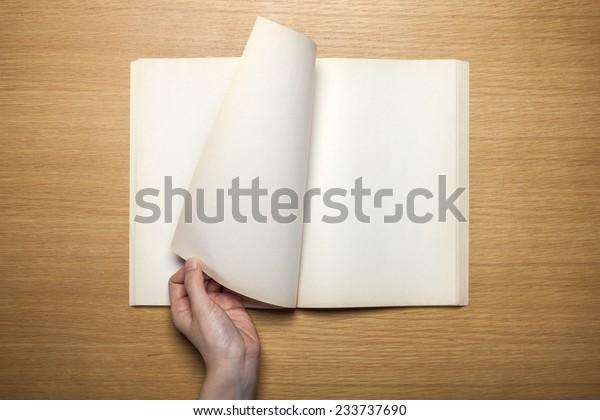 一個女性手握住(握)一個復古(舊)書(注,日記)傳播,並通過一本書在木桌上,頂部視圖在工作室的頁面。