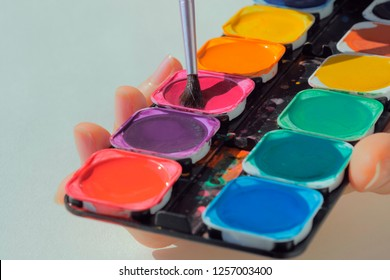 Female hands holding art palette with paints and paintbrush against white background