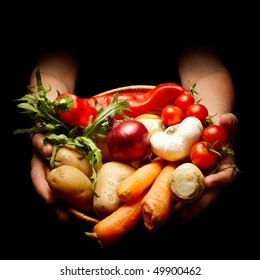 female hands holding a basket full of vegetables isolated on black