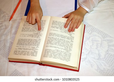 Female hands holding a big book, on a white table, reading,