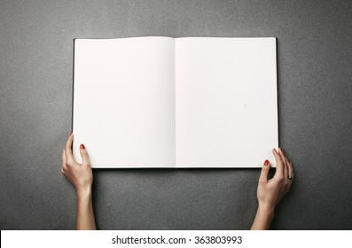 Female hands holding a big open book. Horizontal