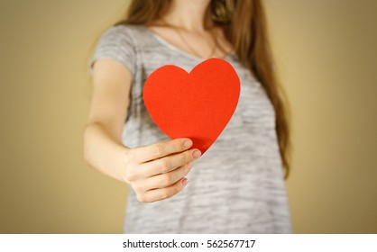 Female hands holding black empty red Valentines card with heart on a white background