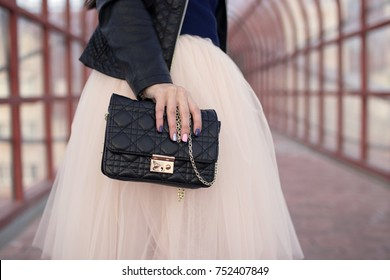 Female hands holding black handbag clutch amid the skirt-tutu pink