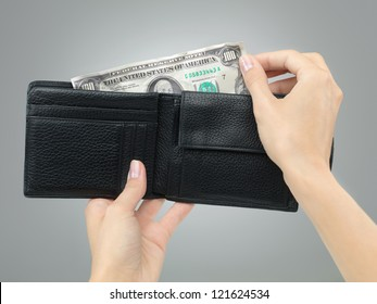 female hands holding a black leather wallet removing crumbled money from it on grey gradient background
