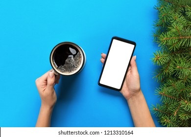 Female hands holding black mobile phone with blank white screen and mug of coffee. Mockup image with copy space. Top view on blue background, flat lay.