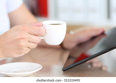 Female hands holding black tablet pc and cup of coffee closeup. Mobile computer with touch screen working as book. Popular gadget, modern lifestyle, business life, morning coffee concept