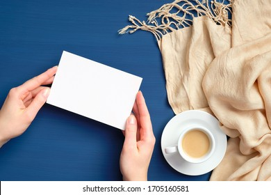 Female hands holding blank paper card mockup over dark blue background with plaid and cup of coffee. Flat lay, top view. Hygge, cozy home, autumn fall concept