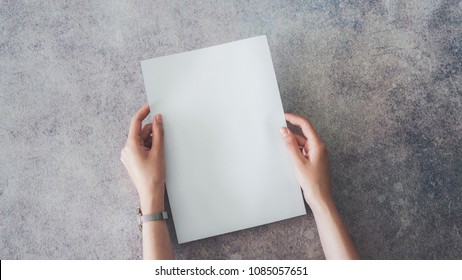 Female hands holding blank white paper
