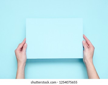 Female hands holding blue paper sheet on blue background. Top view. Mockup, copy space, minimalism