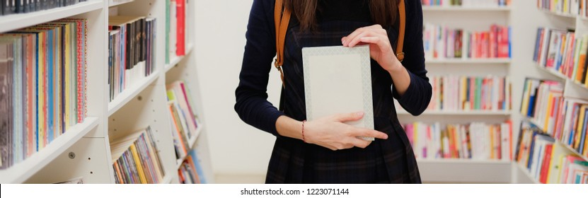 Female hands holding a book in shop on background of bookshelves. Girl choosing what to read in bookstore