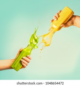 Female hands holding bottles with yellow and green splash smoothie or juice on blue background with tropical leaves and fruits. Summer beverages concept.