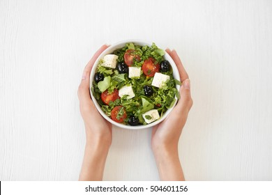 Female hands holding bowl with green lettuce salad isolated on white