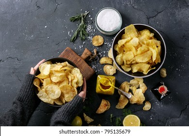Female hands holding the bowl of home made potato chips served with mustard, rosemary, fleur de sel salt, lemon on stone background. Top view. Copy space