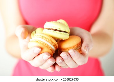 Female hands holding box with colorful french macaroons