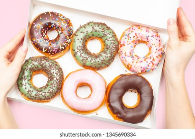 Female hands holding box with donuts. Colorful donuts in box on pastel pink background