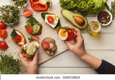 Female hands holding bruschettas with cheese, egg, microgreen and tomato. Healthy vegetarian sandwiches at kitchen table with various vegetables bowls and greens. Cooking food background, top view