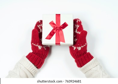Female hands holding christmas gift box in red mittens