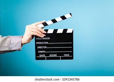Female hands holding a clapperboard