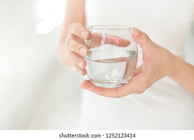 Female hands holding a clear glass of water.A glass of clean mineral water in hands, healthy drink