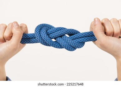 Female hands holding a climbing rope with a secure node. Safety.