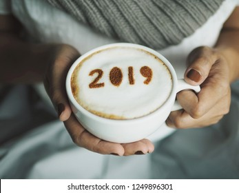 Female hands holding coffee cup with the number 2019 on frothy surface, blurred background of white dress with grey scarf. Holidays food art creative concept image for active days in New Year 2019.