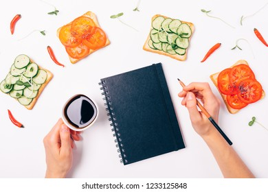 Female hands holding coffee and pencil near closed notepad, top view. Flat lay decorative frame of toasts with cucumbers and tomatoes, chili peppers and sprouts on white background.