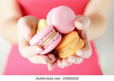 Female hands holding colorful french macarons