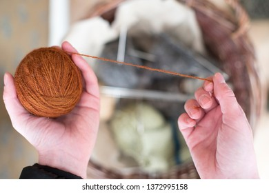 Female hands holding colorful orange balls of Yarn with thread on basket with wool background in rural setting.
