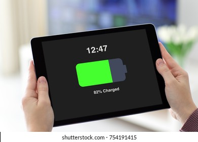 Female hands holding computer tablet with charged battery on screen in room home