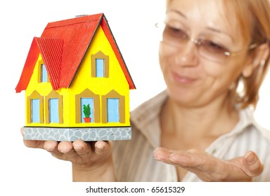 Female hands holding concept house. Selective focus on the house