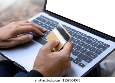 Female hands holding credit card, using laptop computer with blank screen for online shopping and payment at home. Internet banking concept.
